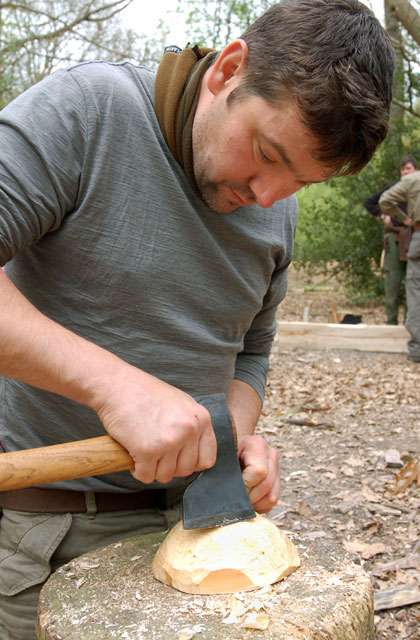 One of the students shaping the outside of a bowl with his axe