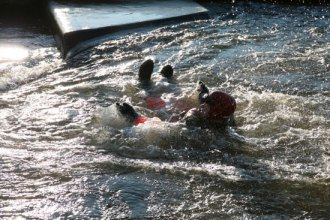 Practising defensive swimming in fast moving water during swift water training