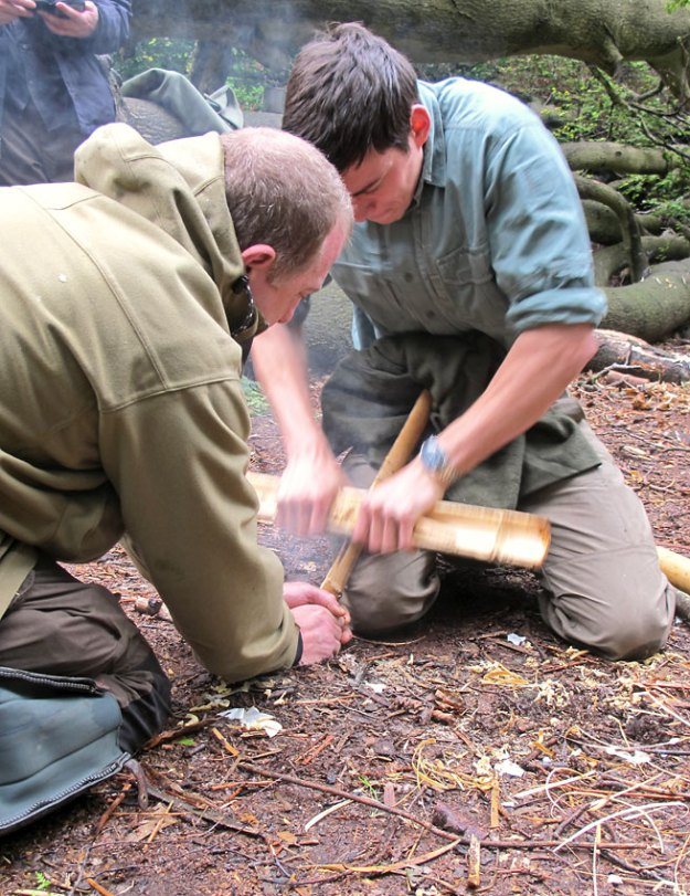 Keith assists Dan Hume in the Bamboo Fire Saw method of friction fire lighting, on Woodlore's Fire Lighting Techniques course